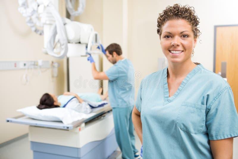 Infirmière Smiling While Colleague préparant le patient image libre de droits