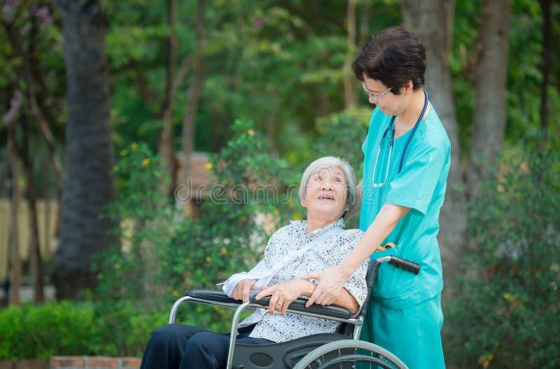 Infirmière supérieure de sourire de travailleur social prendre pour s'inquiéter un patient supérieur sur le fauteuil roulant pour photos stock