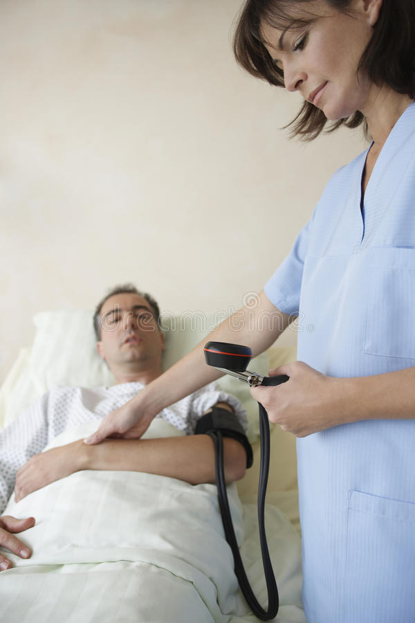Infirmière Taking Blood Pressure et impulsion de patient photographie stock