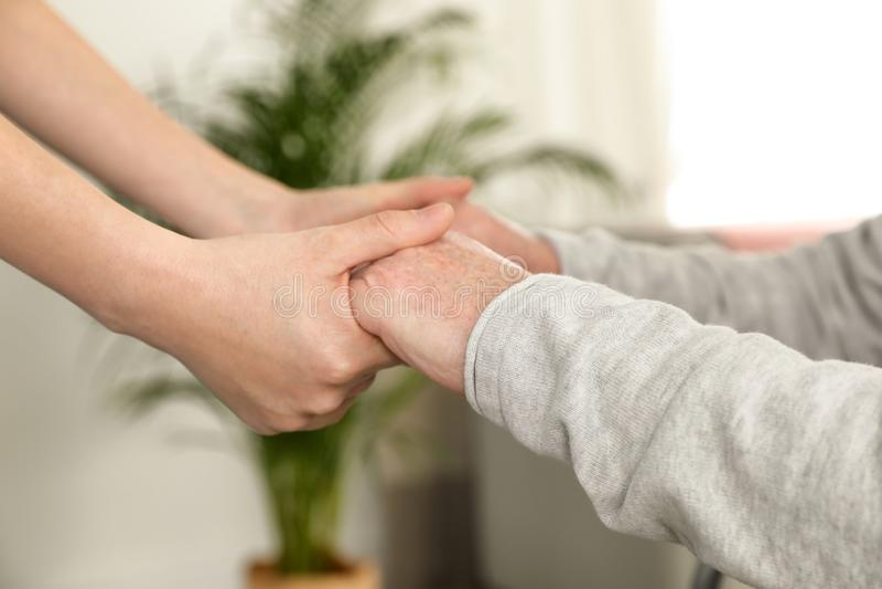 Infirmière tenant les mains de l'homme plus âgé à l'intérieur, plan rapproché Soutien de l'aîné image libre de droits