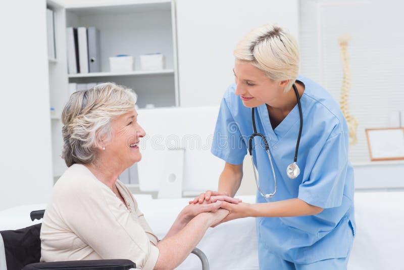 Infirmière tenant les mains supérieures de patients dans la clinique image stock