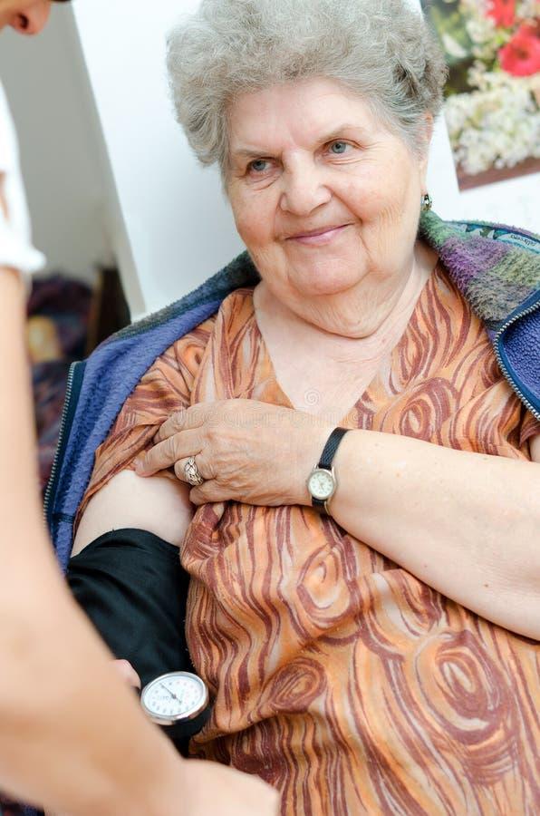 Infirmière vérifiant la tension artérielle supérieure de femme photographie stock