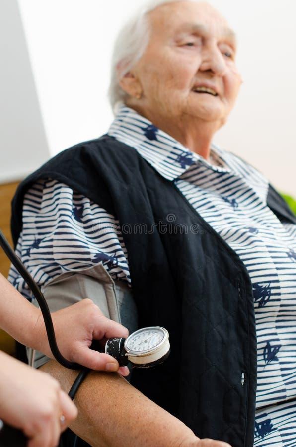 Infirmière vérifiant la tension artérielle supérieure de femme photos libres de droits