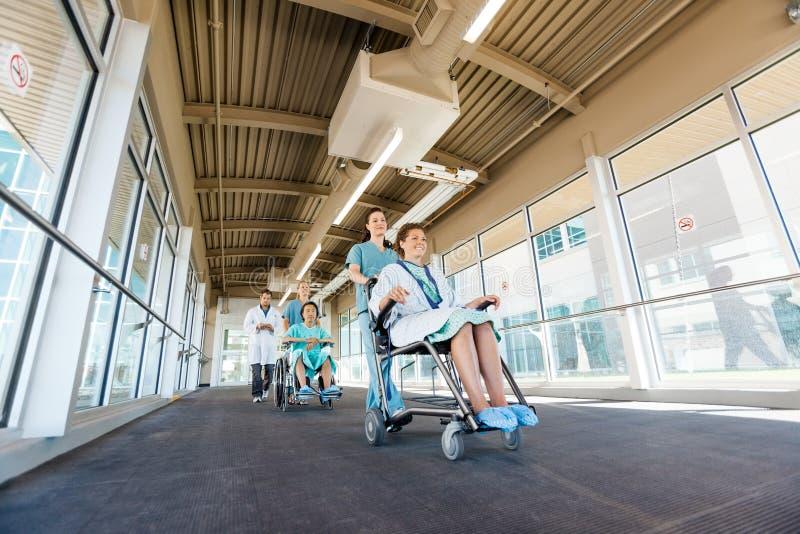 Infirmières poussant des patients sur des fauteuils roulants à l'hôpital photos libres de droits
