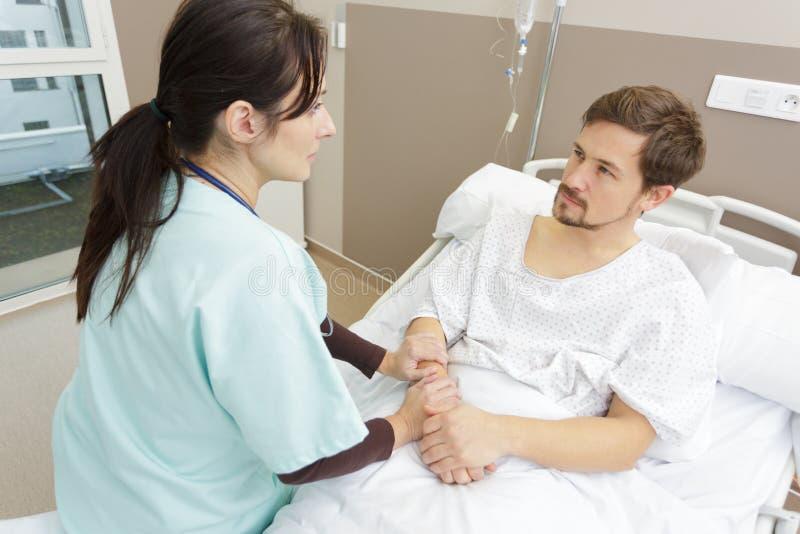 Infirmi?re s?re With Patient Resting dans l'h?pital images stock