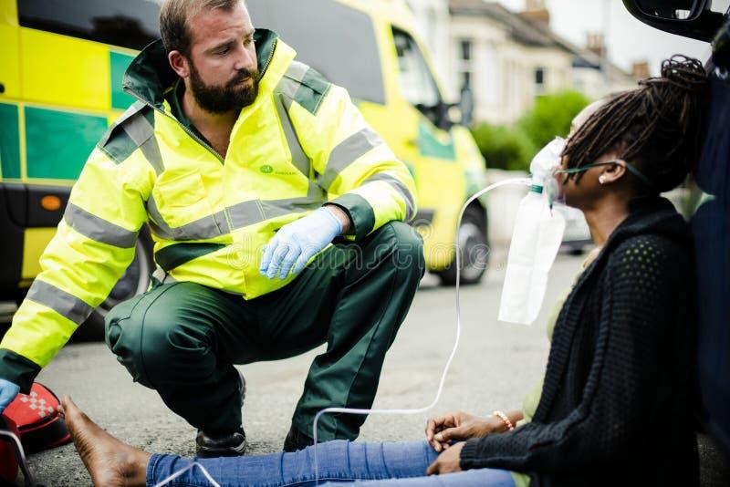 Infirmier masculin mettant sur un masque à oxygène à une femme blessée sur une route image libre de droits