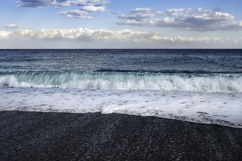 Inflamaciones que se estrellan en la playa pebbled negra en Sicilia imagenes de archivo