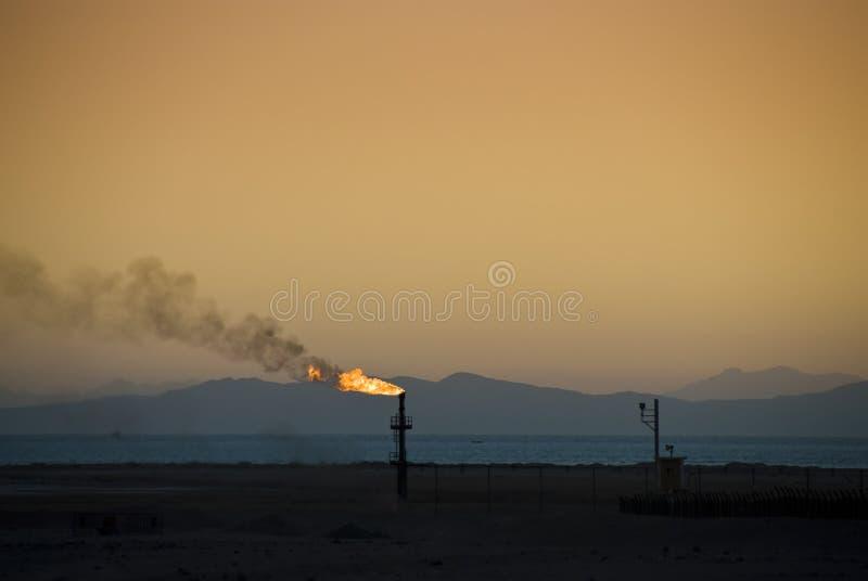Inflame-se de uma tubulação de petróleo no por do sol. imagens de stock