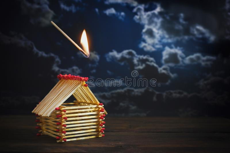 Inflamed match is falling on a house built of matches against a dark stormy sky with copy space, insurance concept for danger or. Financial  risk in real estate royalty free stock photos