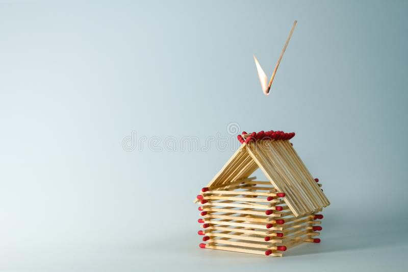Inflamed match is falling on a house built of matches, light blue background with large copy space, insurance concept for real. Estate investment risk or life stock photo