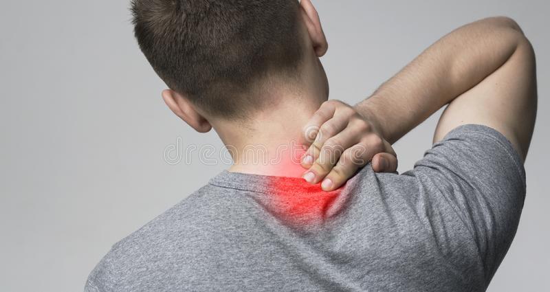 Young man massaging his sore neck, back view. Inflammation of vertebrae. Young man massaging his sore neck, back view, panorama royalty free stock photos