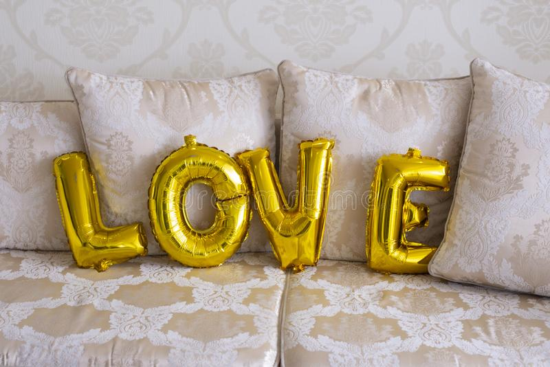 Inflatable balloons in the form of letters. Golden letters Love royalty free stock photo