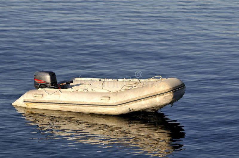 Inflatable boat. Cream inflatable boat on the sea water stock photography