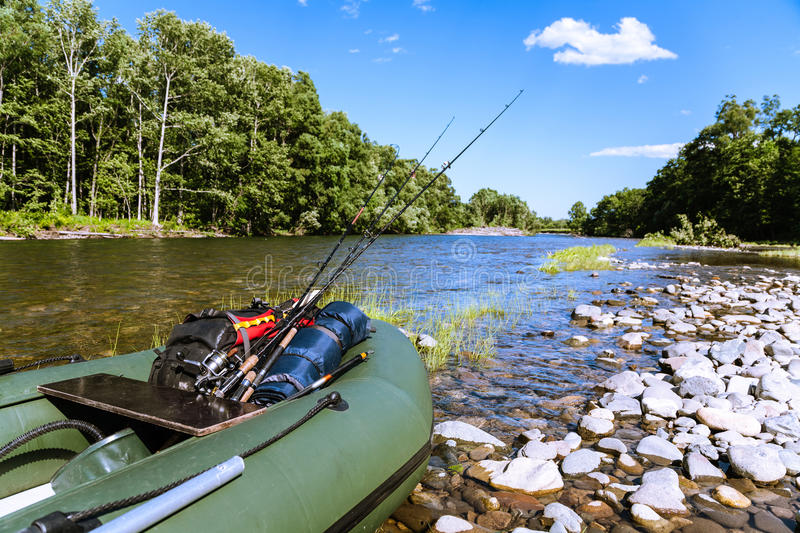 Inflatable boat fishermen. On the river bank stock photos