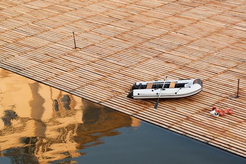 Inflatable boat and helmets on the wooden flooring on the water, the reflection of the building in the water stock photography