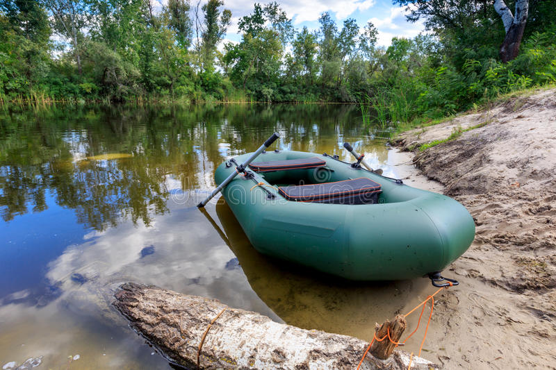 Inflatable boat on lake shore. In summer forest stock photos