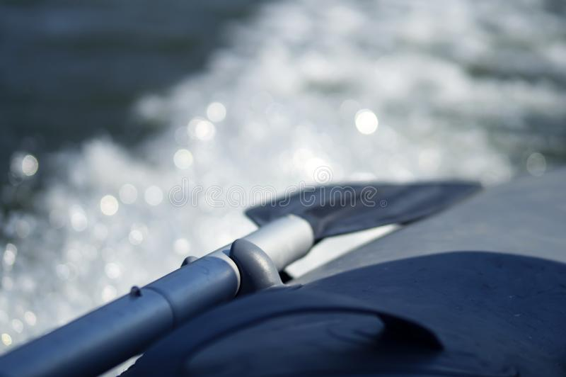 Inflatable boat paddle. The paddle is tied to an inflatable boat that goes on water at speed royalty free stock image