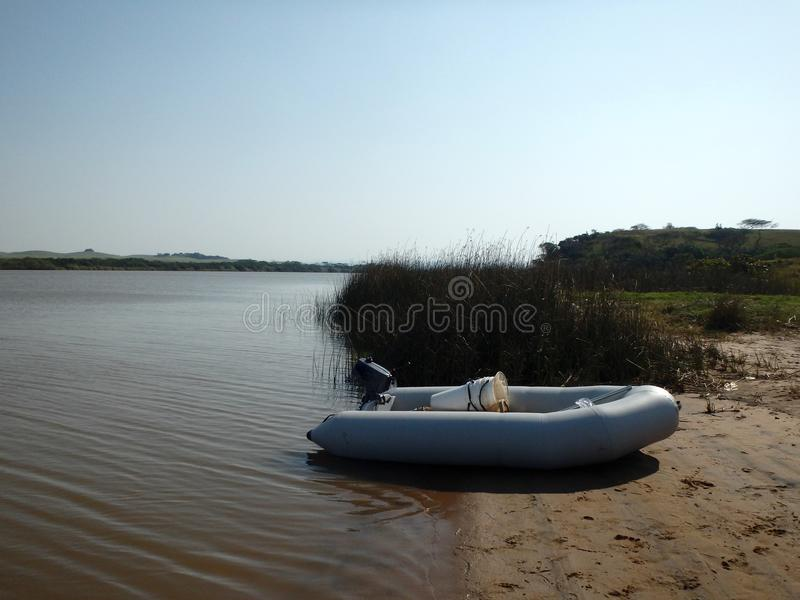 Inflatable boat on a river bank stock photography
