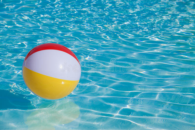 Inflatable colorful ball floating. In a swimming pool stock image
