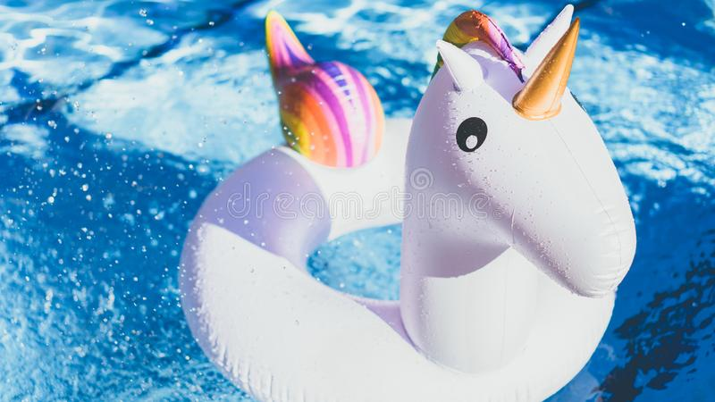 Inflatable colorful white unicorn at the swimming pool. Vacation time in the swim pool with plastic toys.Splash Water in royalty free stock image