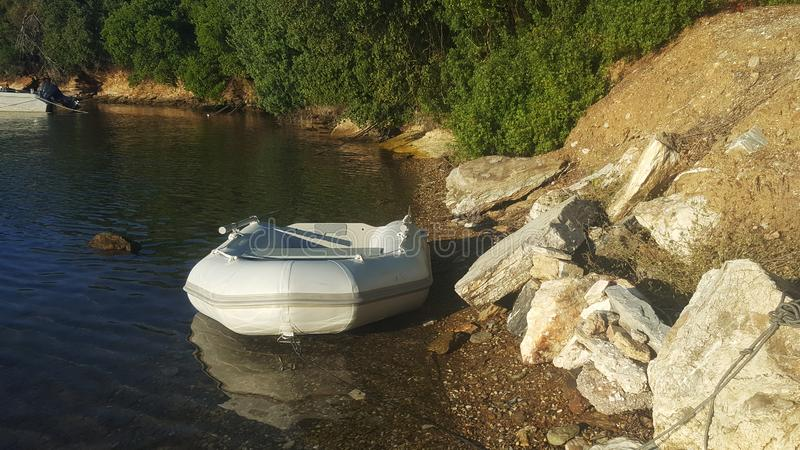 Inflatable dinghy moored. On the shore of a wild place royalty free stock photo