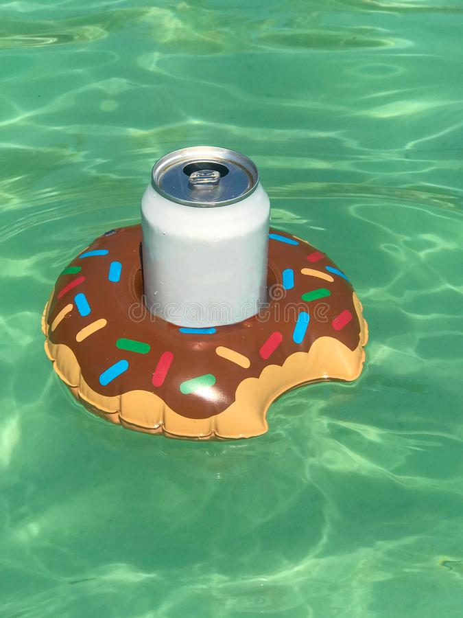 Inflatable drink holder with soft drink in swimming pool on sunny day. Space for text royalty free stock photo