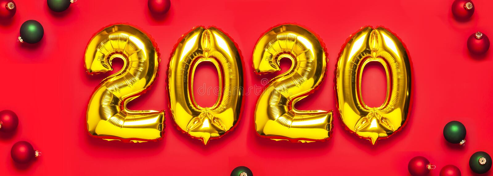 2020 inflatable golden numbers with red and green christmas balls on red background. New year winter decoration, holiday symbol, stock photography