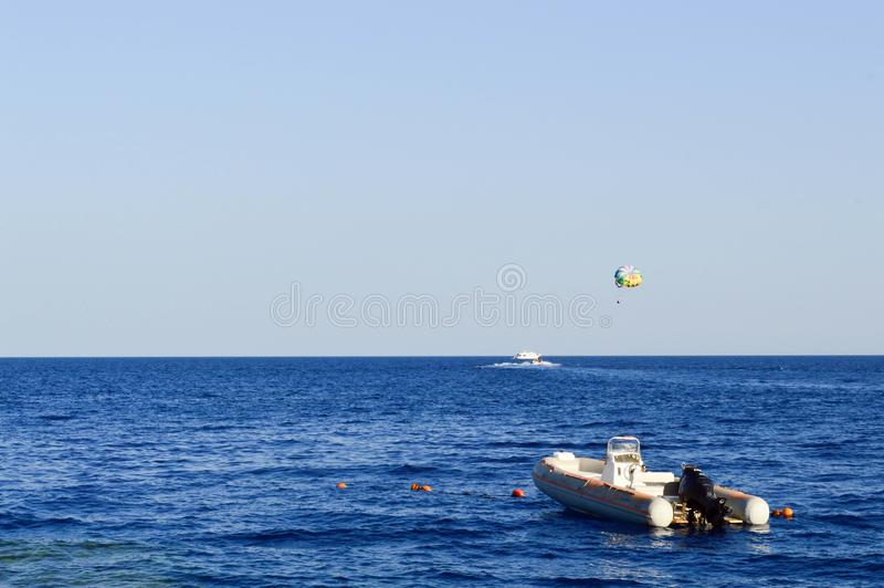 Inflatable gray motor boat with a helical engine on a salt beautiful sea against a background of paraseyling and a blue sky royalty free stock images