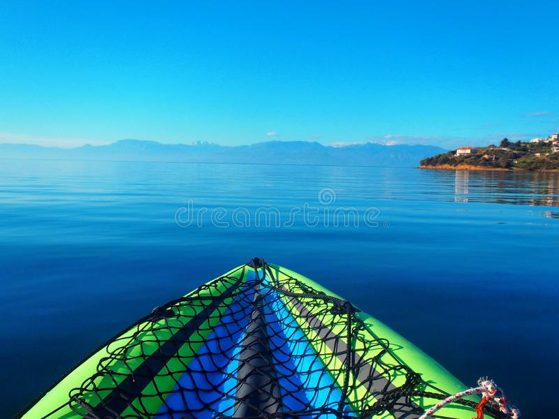 Inflatable Kayak in Calm Gulf of Corinth Water, Greece. A  brightly coloured in inflatable kayak floating in calm Gulf of Corinth sea water, with hazy view to royalty free stock photo