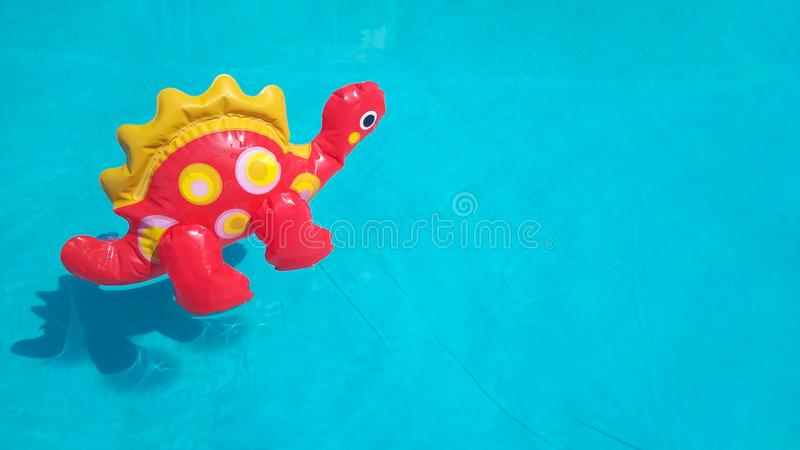 Inflatable mini dinosaur on pastel blue background, pool float party, trendy summer concept. Flat lay, top view, copy stock images