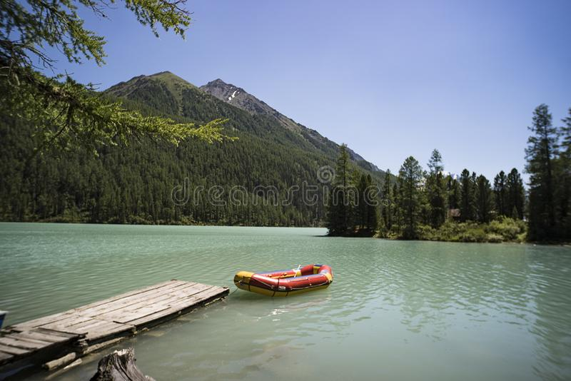 inflatable red boat in the belterwiede lake. Red boat at the wooden bridge in the blue lake. Siberia Altai. wilderness. Russia fis stock photos