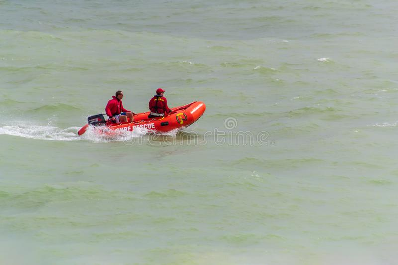 An inflatable rescue boat with surf lifesavers patrolling the beach at Eastbourne UK, August 2019 royalty free stock image