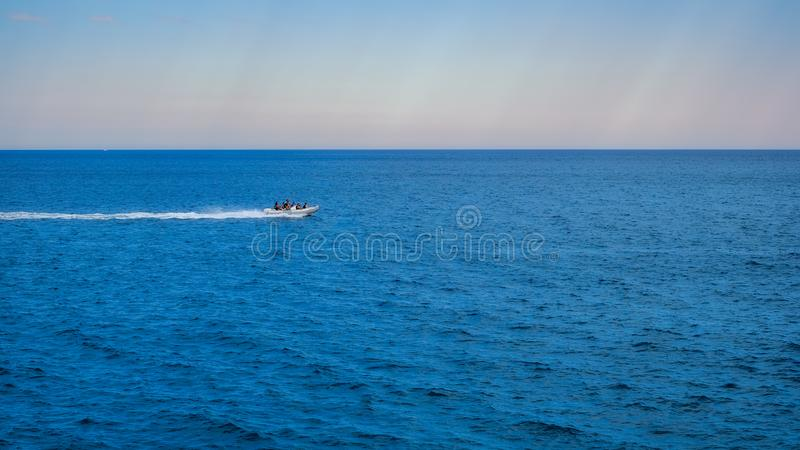 Inflatable rib boat cruising in high speed in clear water sea. Panorama royalty free stock images