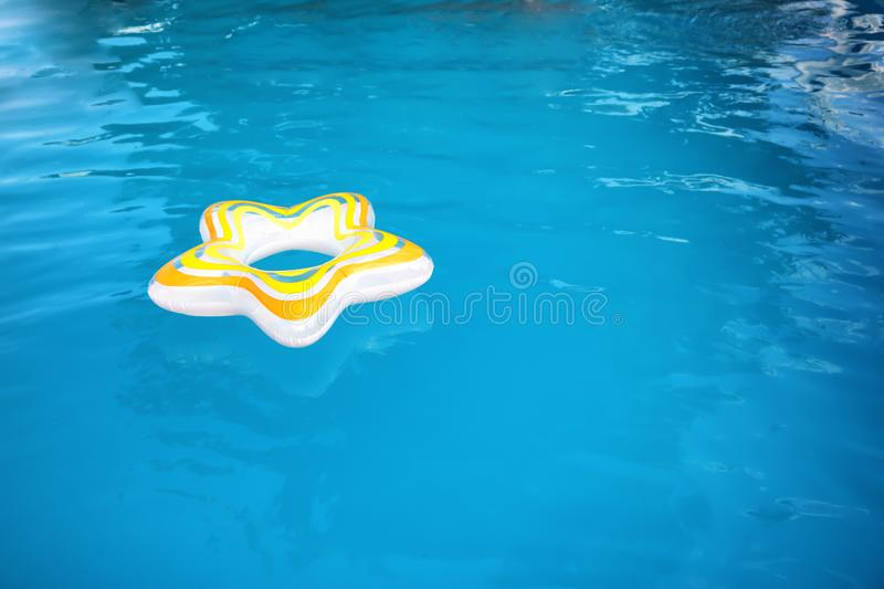 Inflatable ring floating in swimming pool. On sunny day stock photos