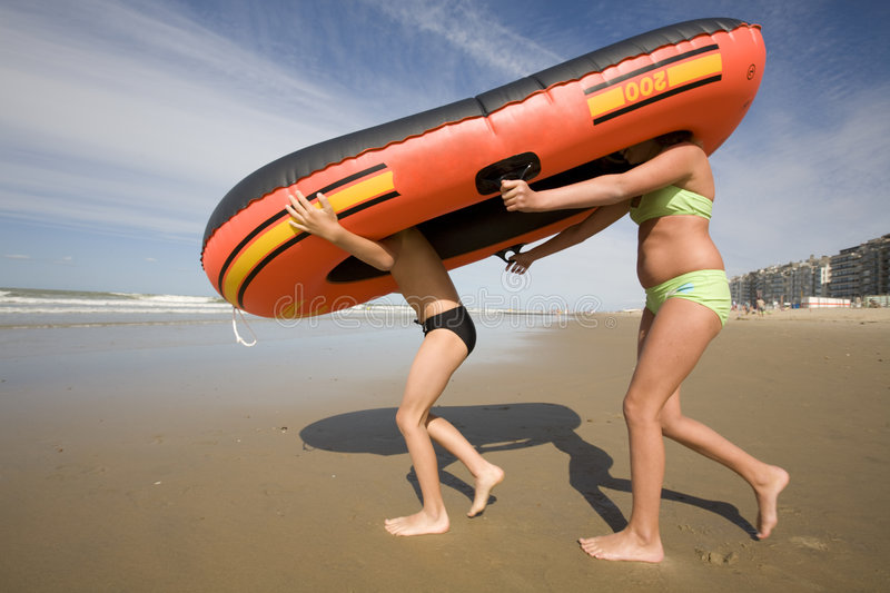 Inflatable rubber boat with legs. Children walking with their inflatable rubber boat at the beach stock photos