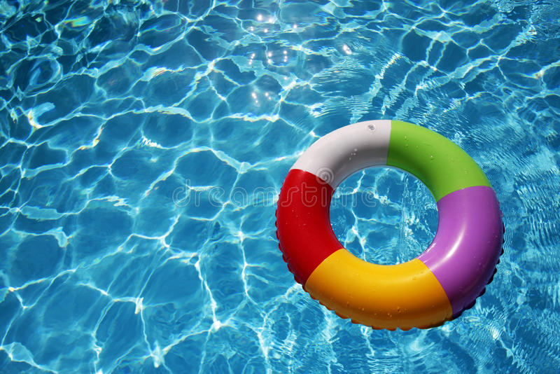 Inflatable Rubber Ring in a beautiful blue pool. Inflatable Rubber Ring floating in a beautiful blue pool stock image
