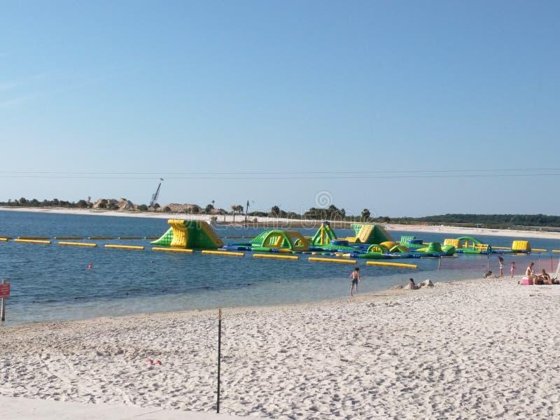 Inflatables auf dem Wasser und den Leuten am Strand lizenzfreie stockfotografie