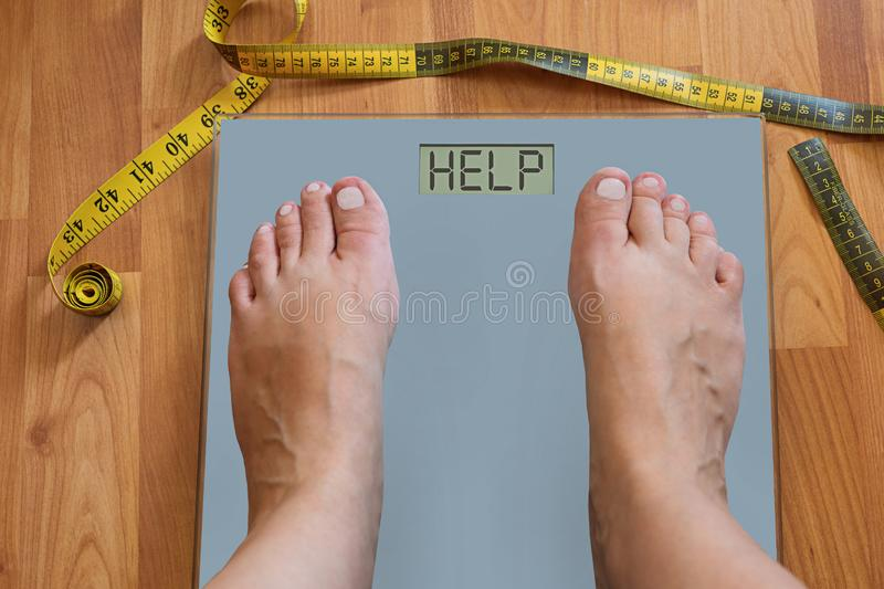 Inflated feet of woman on weighting scale asking for help to lose weight. Diet concept royalty free stock images