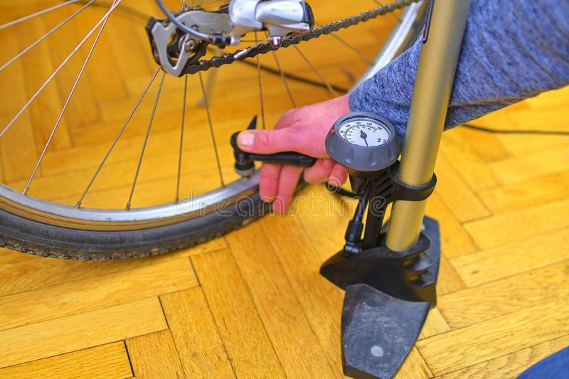 Inflating the tire of a bicycle. Cyclist repairs bike. Bicyclist pumping air into the wheel. Biker uses a bicycle pump. Pumping air into a wheel of bike. Home stock images