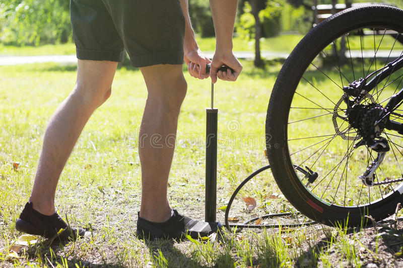 Inflating the tire of a bicycle. Cyclist repairs bike in forest. Bicyclist pumping air into the wheel. Biker uses a bicycle pump. stock photo