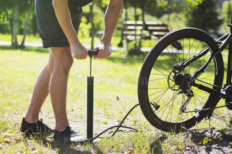 Inflating the tire of a bicycle. Cyclist repairs bike in forest.Inflating the tire of a bicycle. Cyclist repairs bike in forest. Inflating the tire of a bicycle stock images