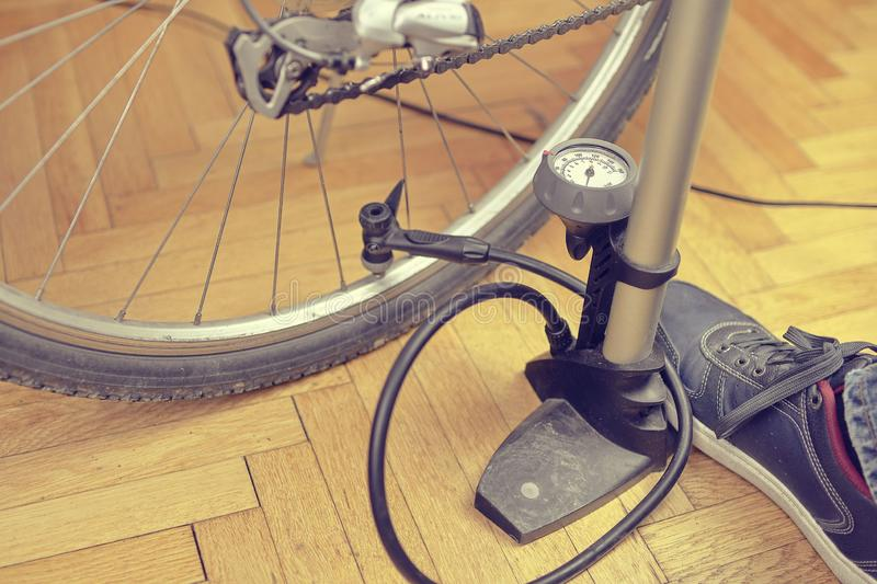 Inflating the tire of a bicycle. Home maintenance of bike. Bicycle service and maintaining for the new season.  royalty free stock photography