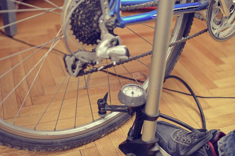 Inflating the tire of a bicycle. Pumping air into a wheel of bike. Home maintenance of bike. Bicycle service and. Maintaining for the new season royalty free stock images
