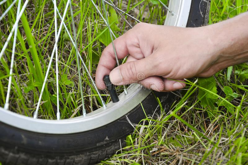 Inflating the tire of a bicycle. Pumping air into a wheel of bike. Home maintenance of bike. Bicycle service and. Maintaining for royalty free stock photos