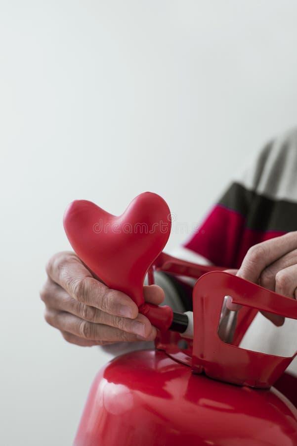 Inflation av en hjärtformad ballong från en cylinder royaltyfri bild