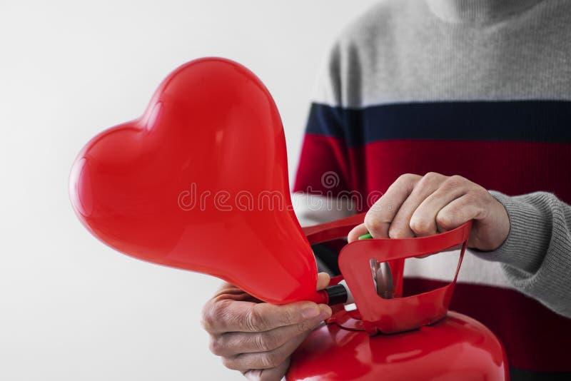 Inflation av en hjärtformad ballong från en cylinder royaltyfri fotografi