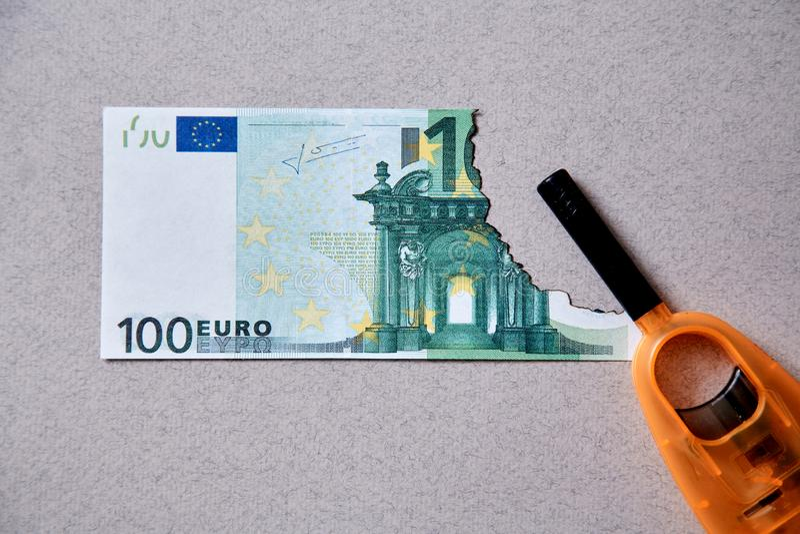 Inflation- och avskrivningpengar, begrepp Konkurs eller finansiella fördärvar och armod Bränd eurosedel och tändare royaltyfria foton