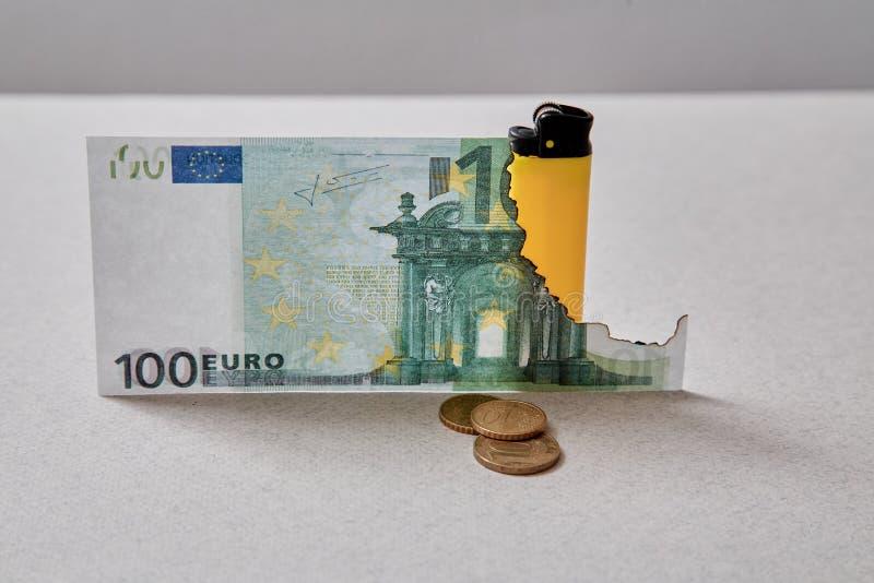 Inflation- och avskrivningpengarbegrepp Konkurs eller finansiella fördärvar och armod Bränd eurosedel och tändare arkivbild