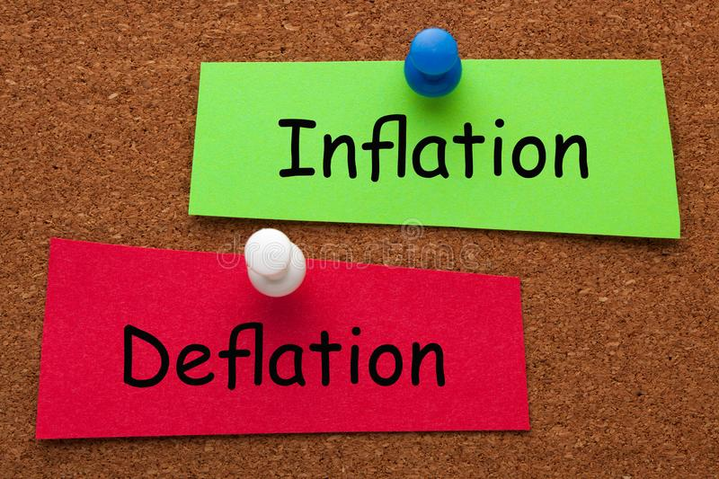 Inflation Deflation Concept. Inflation versus Deflation words on colorful stickers pinned on cork board. Business concept royalty free stock image
