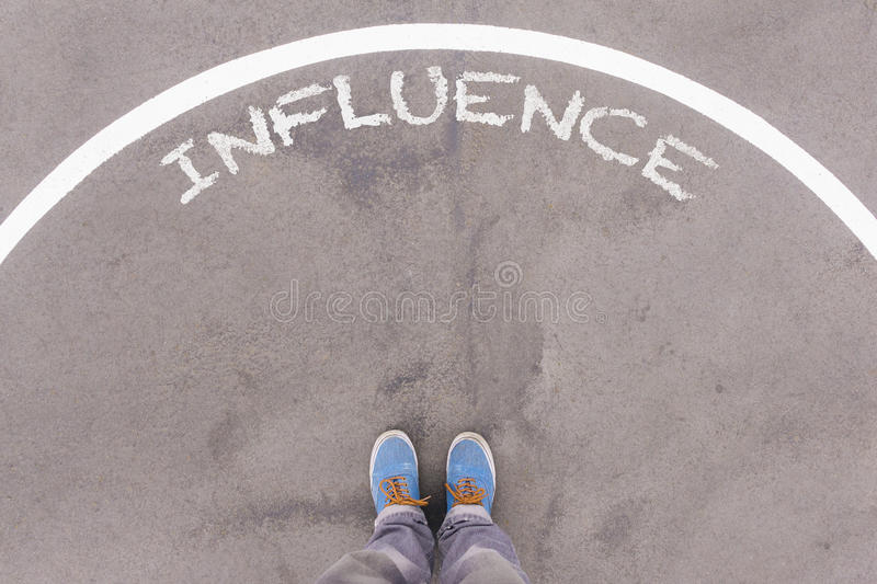 Influence text on asphalt ground, feet and shoes on floor. Personal perspective footsie concept stock photo